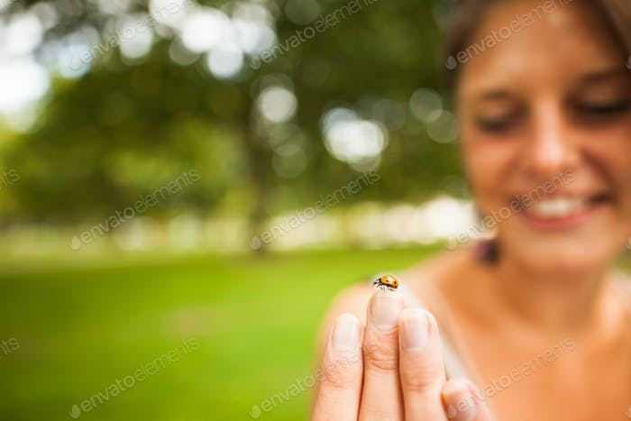 Close-up of a smiling blurred young woman gently holding a ladybug at a park