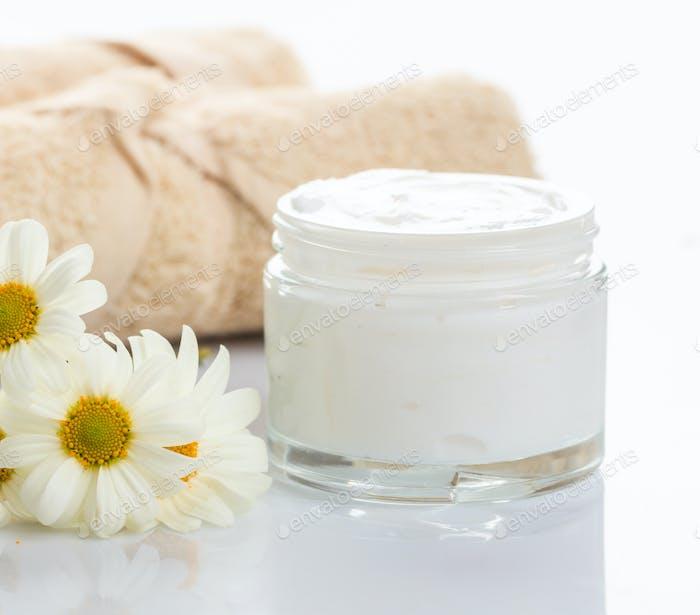 Moisturizing cream in glass jar and chamomile on white background.