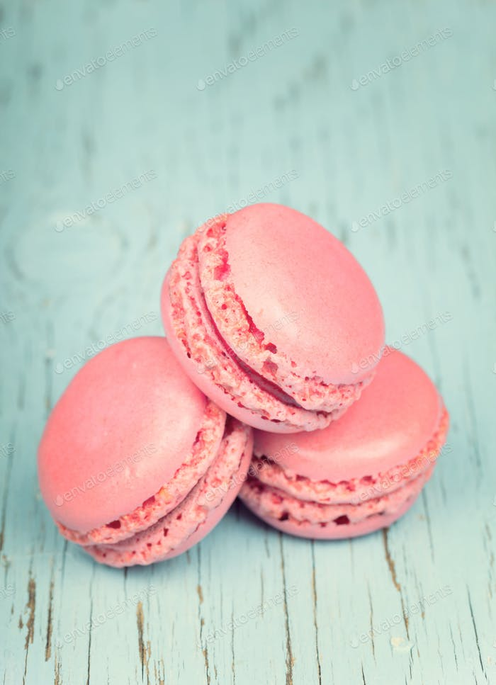 Two pink macaroons on wooden baby blue background