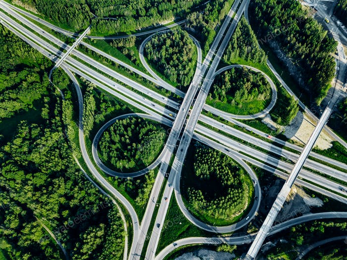Aerial top view of Highway and overpass with green forests in Finland.