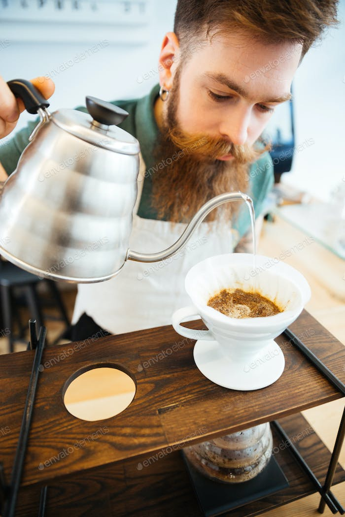 Barista pouring water on coffee ground with filter