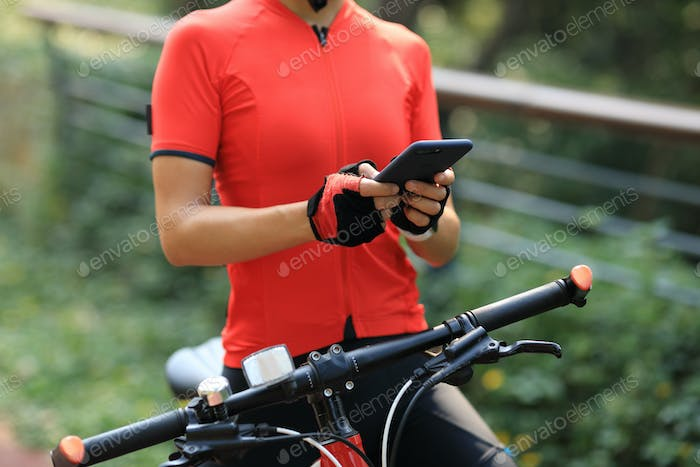 Woman biker using smartphone in park
