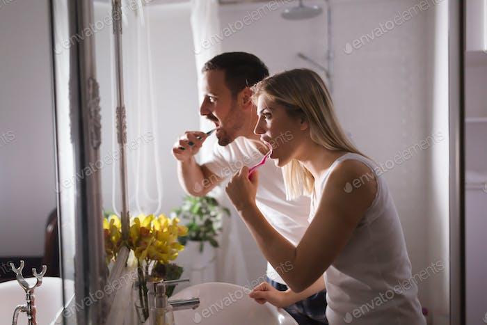 Attraktives Paar Zähne am Morgen zusammen waschen