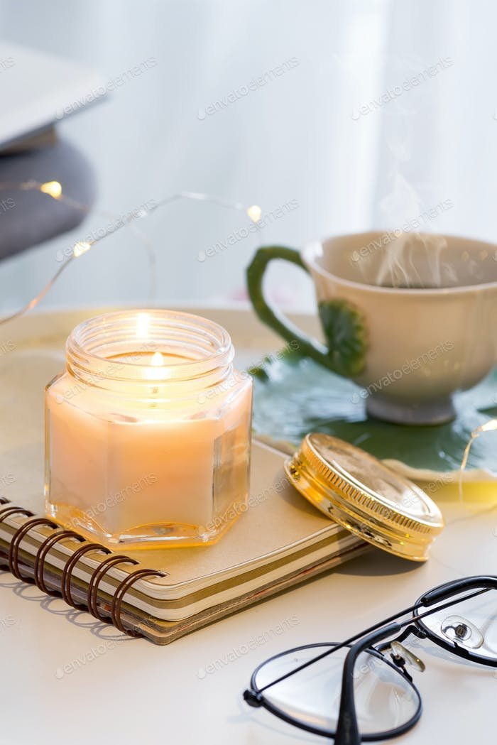 A candle with a notebook, cup of tea on a table with a chair, a plaid and a book. Home interior