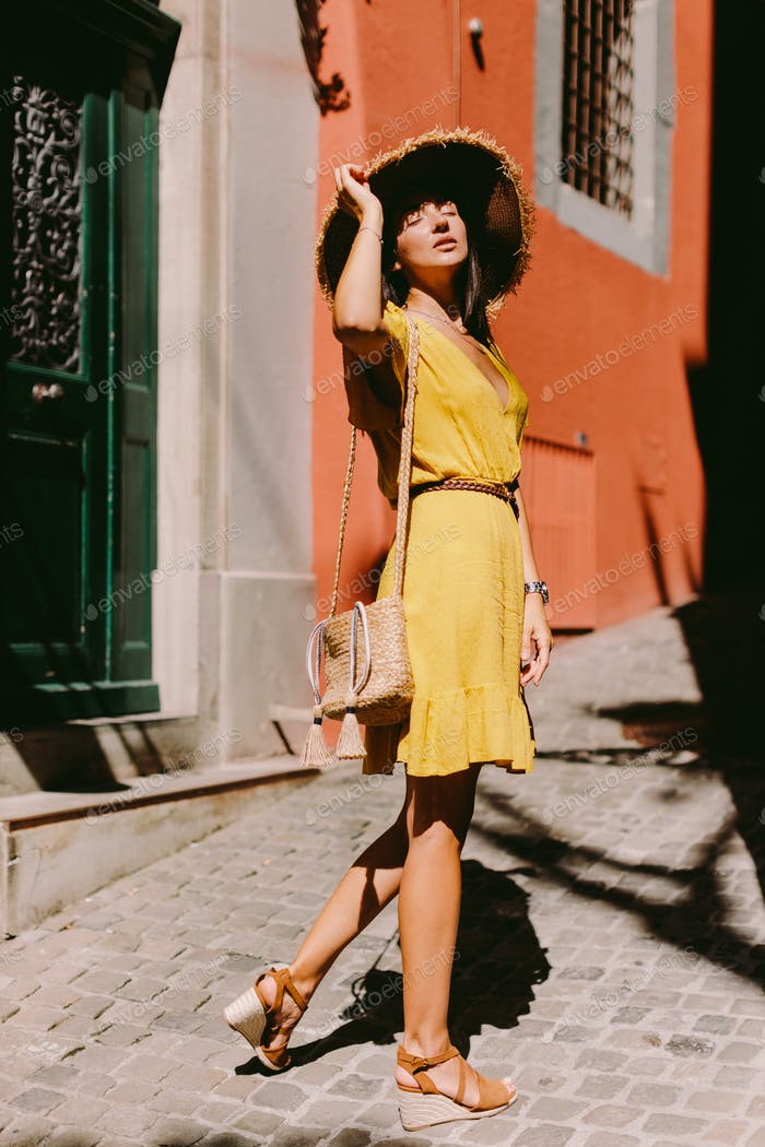 attractive woman in summer dress and straw hat with handbag walking