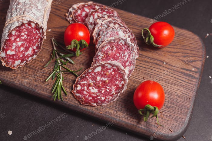 Smoked ham sausage and cutted slices with rosemary and cherry tomatoes on dark wooden board
