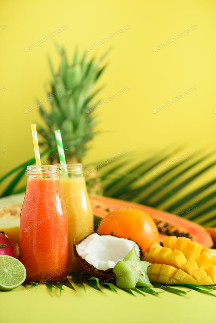 Juicy papaya and pineapple, mango, orange fruit smoothie in two jars on yellow background. Detox