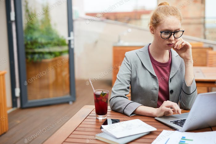 Businesswoman working in outdoor cafe