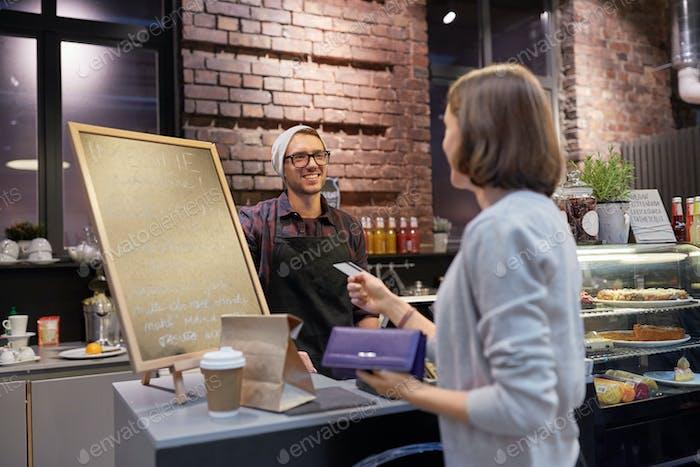 Barmann und Frau zahlen mit Kreditkarte im Café