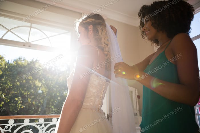 Beautician adjusting veil on bride hair at home