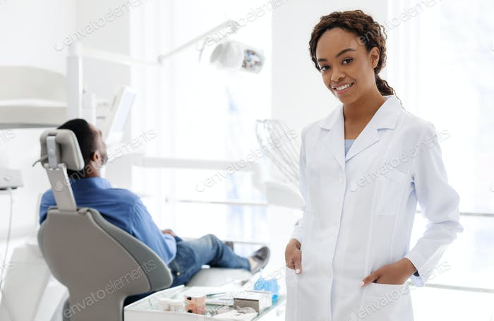 Pretty african woman dentist in dental clinic
