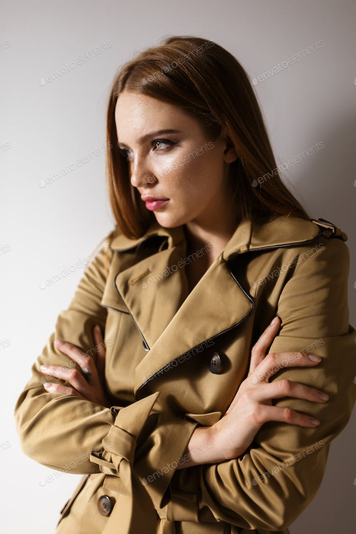 Portrait of young beautiful lady in trench coat standing and thoughtfully looking aside