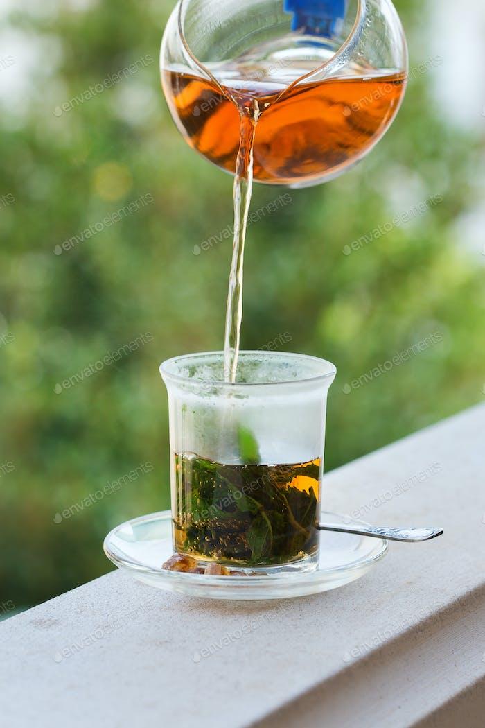 Glass of hot mint tea, traditional moroccan moorish beverage