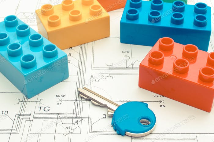 Bunte Bausteine und Hausschlüssel auf Wohnplan. Bauhauskonzept