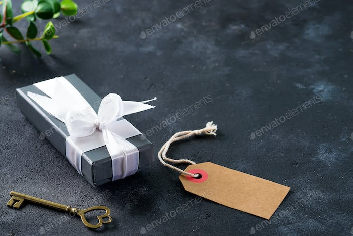 A gray gift box with an old key on dark stone background with copy space. Valentines holiday