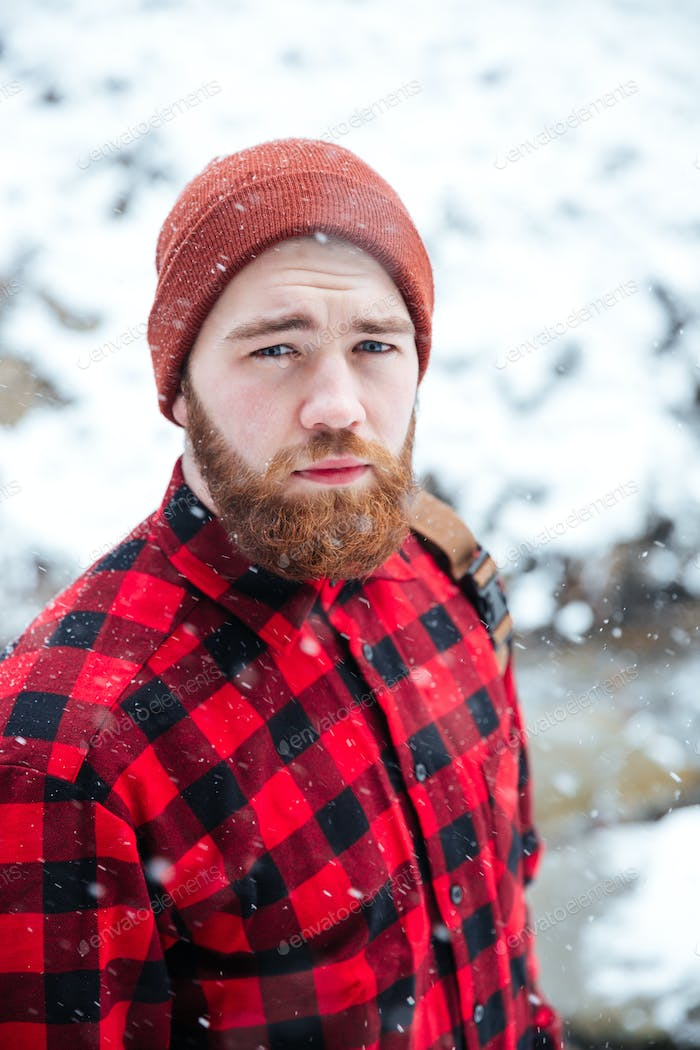 Serious handsome bearded man outdoors in snowy weather