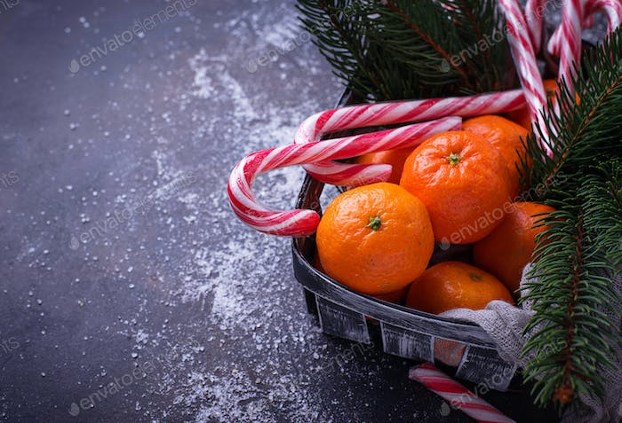 Tangerines and candy cane. Christmas background