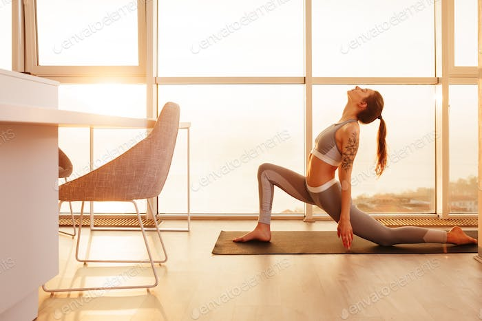 Lady in sporty top and leggings practicing yoga on yoga mat with beautiful view on background
