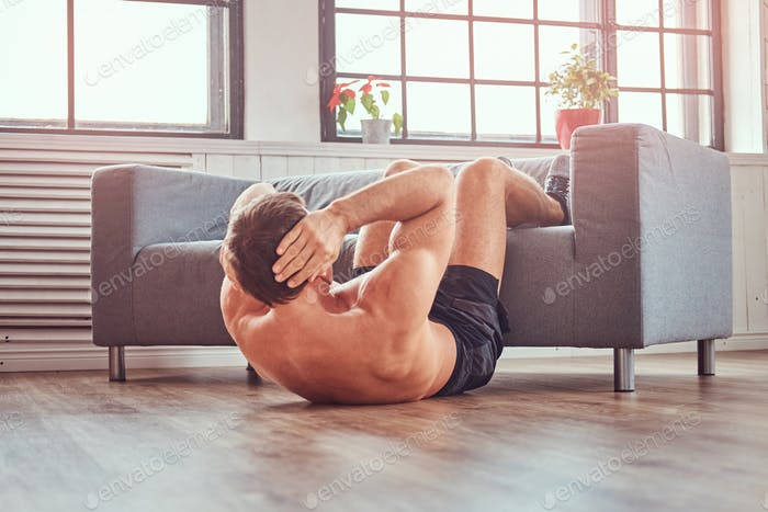 Handsome shirtless muscular male doing abdominal exercises on floor at home., leaning on a sofa.