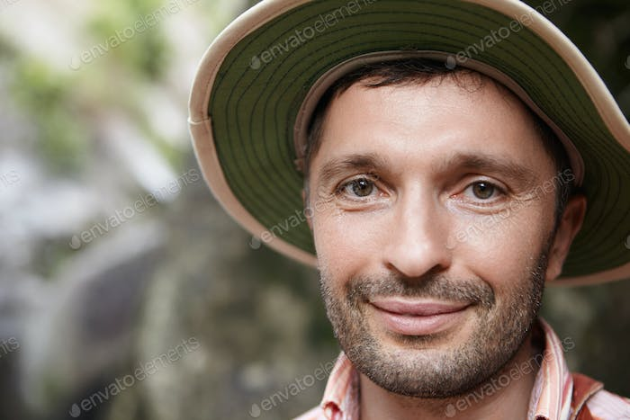 Close up of handsome ecologist with stubble and joyful smile posing outdoors at rocks while working