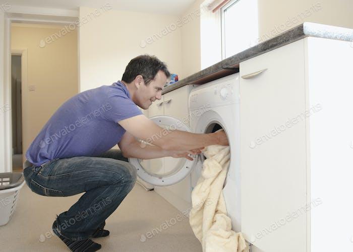 Un hombre poniendo la ropa en la lavadora.