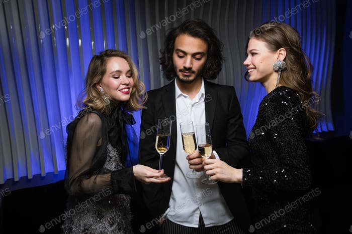 Three young elegant friends cheering up with champagne during celebration