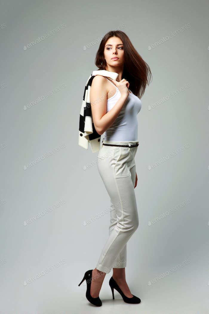 Young beautiful businesswoman in casual clothes looking away on gray background