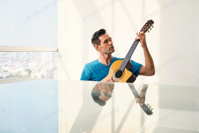 Young Musician Playing Guitar At Home