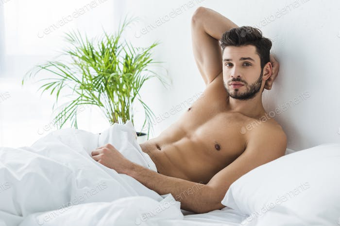 handsome shirtless man resting in white bed