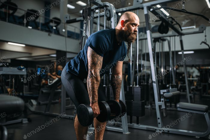 Strong athlete with dumbbells, training in gym
