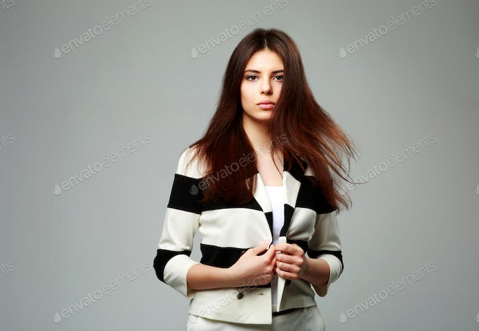 Portrait of a young beautiful woman in casual clothes on gray background