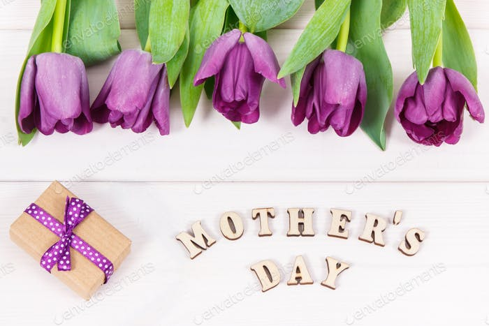Purple tulips and gift for mother's day on white boards