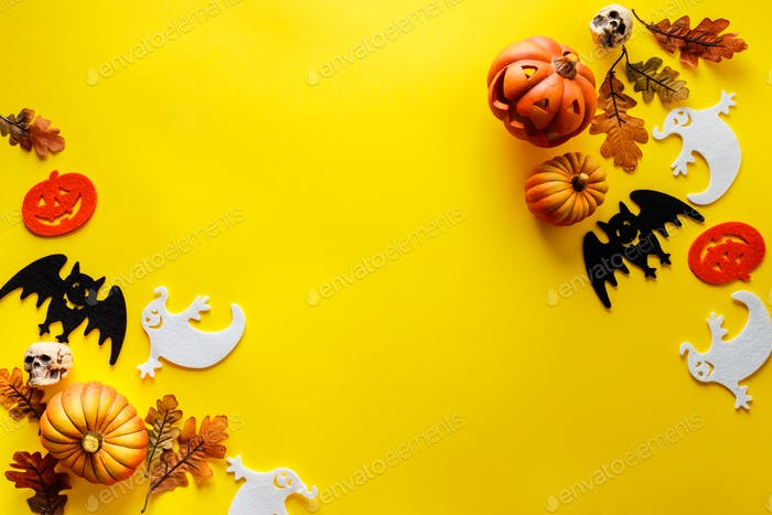 Pumpkins with Halloween decorations on yellow background