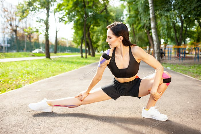 Flexible woman with kinesiology taping practicing lunges outdoors
