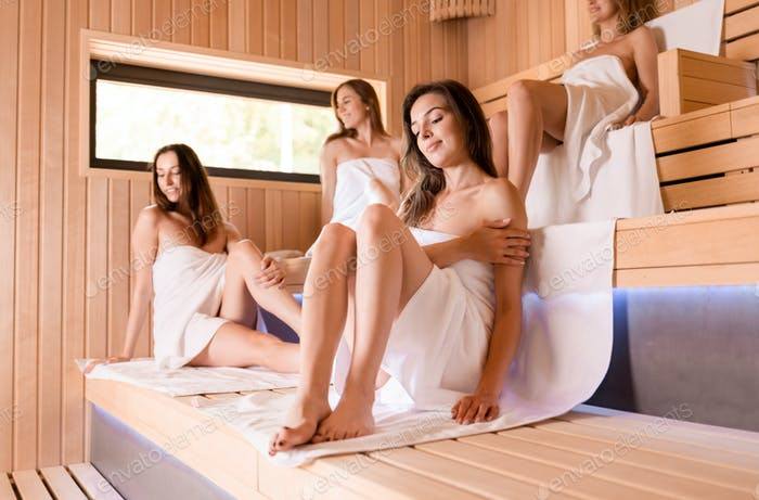 Women pursuing healthy lifestyles relaxing in sauna