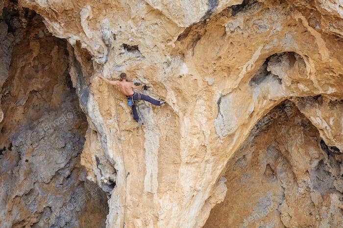 Männlicher Kletterer auf einem Gesicht einer Klippe
