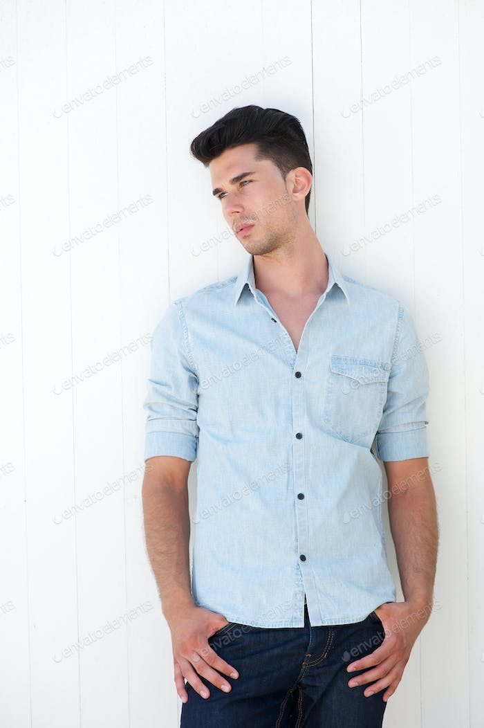 Cute guy standing outdoors with hands in pocket