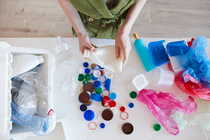 Woman Sorting Plastic at Home Top View
