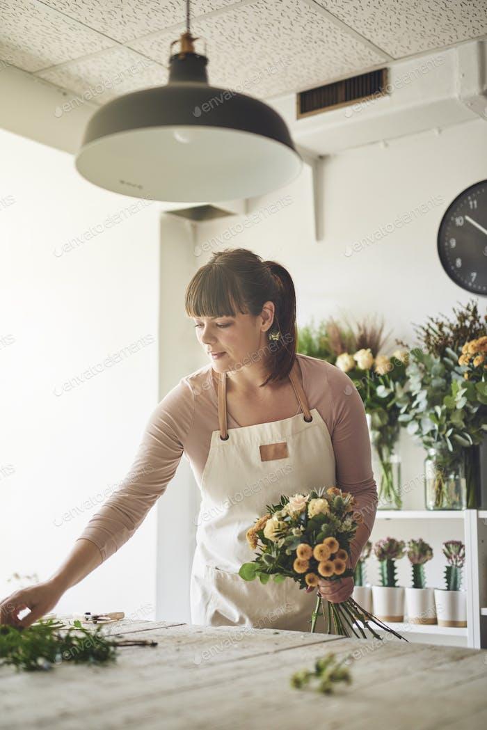 Female florist making a floral arrangement in her flower store
