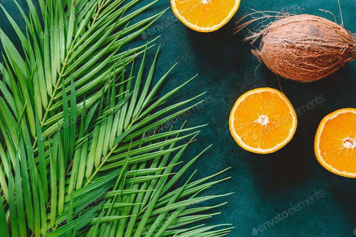 Summer flat lay with palm leaf, oranges and coconut over dark green background.