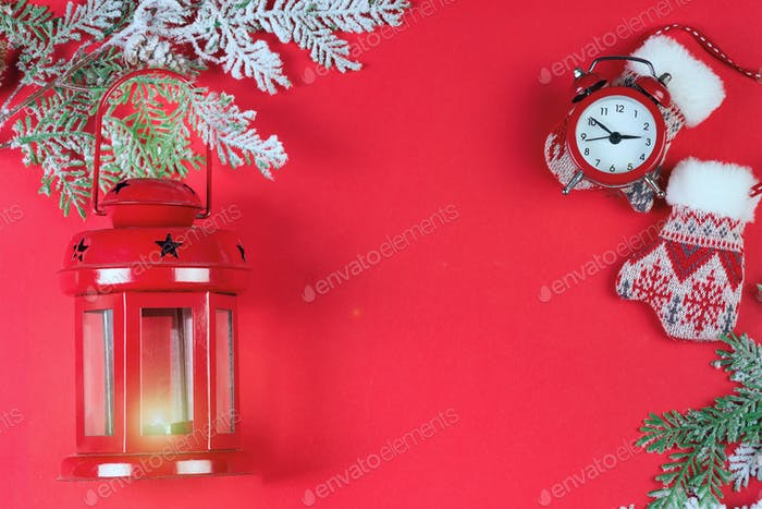 Christmas greeting card with red lantern, red clock, snow branches and mittens on red background