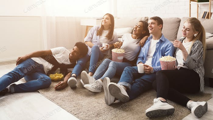 Happy friends watching comedy movie at home