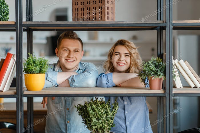 Young smiling couple at the shelf with home plants