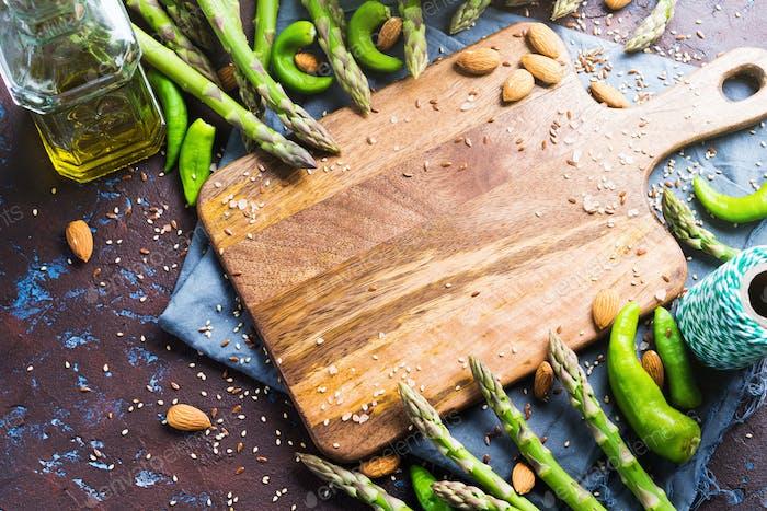 Schneidebrett aus Holz mit Spargel, Nüssen, Salz