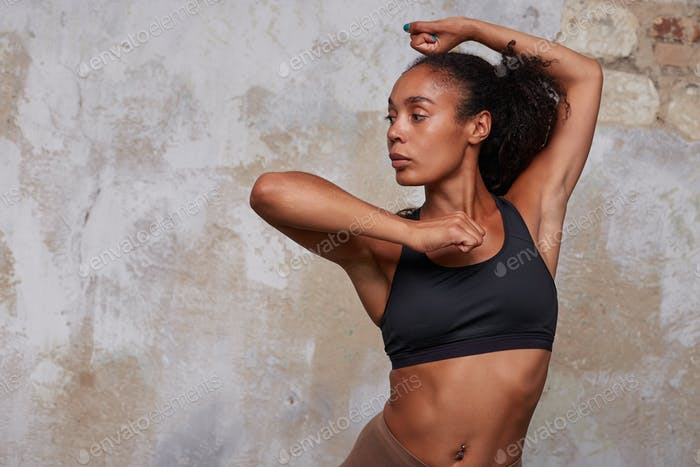 Studio photo of sporty young dark skinned curly woman in black athletic top
