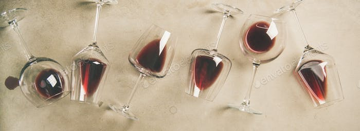 Red wine in glasses over grey concrete background, wide composition