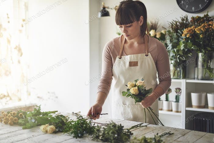 Female florist making a flower arrangement in her shop