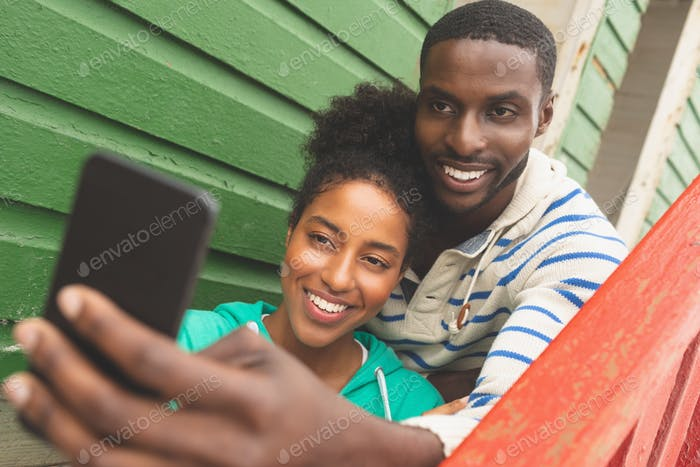Front view of happy Multi-ethnic couple taking selfie while sitting on beach hut