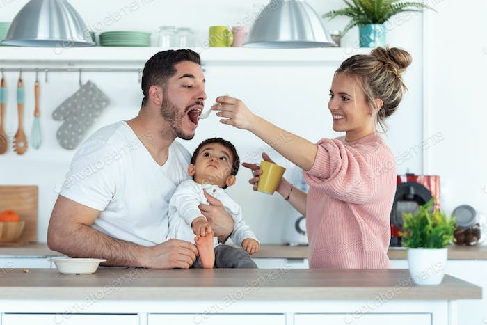 Pretty young mother feeding her husband while her baby looking at them in the kitchen at home.