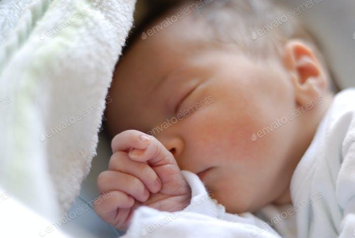 Newborn baby girl in hostpital bed sleeping